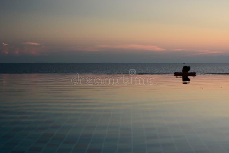 Sylwetka kobieta wśrodku nieskończoność basenu przy zmierzchem Sai Daeng zatoka koh Tao Tajlandia obraz royalty free