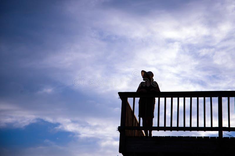 Sylwetka kobieta wspaniały kształt w kapeluszowej pozyci na balkonie dalej zdjęcia stock