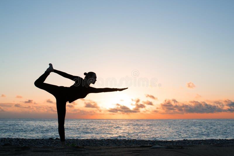 Sylwetka kobiety ćwiczy joga na plaży przy zmierzchem obraz royalty free
