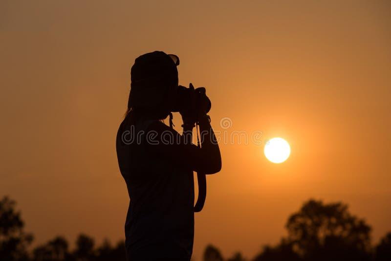 Sylwetka kobiety mienia kamera bierze obrazki outside podczas wschód słońca lub zmierzchu obraz royalty free