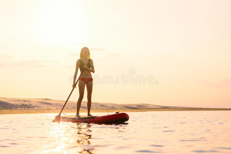 Sylwetka kobiety pozycja na paddle desce obrazy royalty free