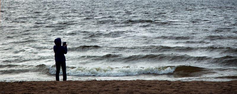 Sylwetka kobiety pozycja na seashore i brać fot zdjęcia stock