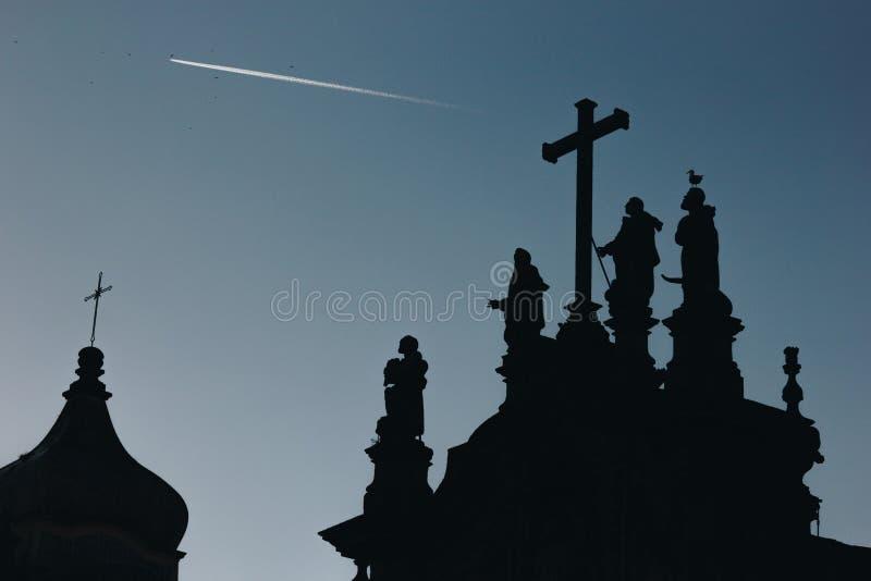 Sylwetka krzyż na kościół nad niebieskim niebem i statuy fotografia royalty free