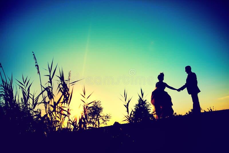 Sylwetka, kształt państwo młodzi przy zmierzchem Nowożeńcy z tłem w naturze zdjęcie royalty free