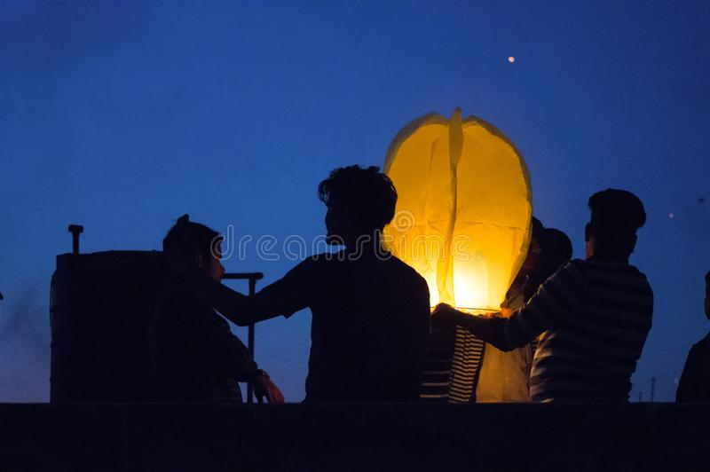 Sylwetka ludzie lata niebo lampion podczas półmroku zdjęcie stock