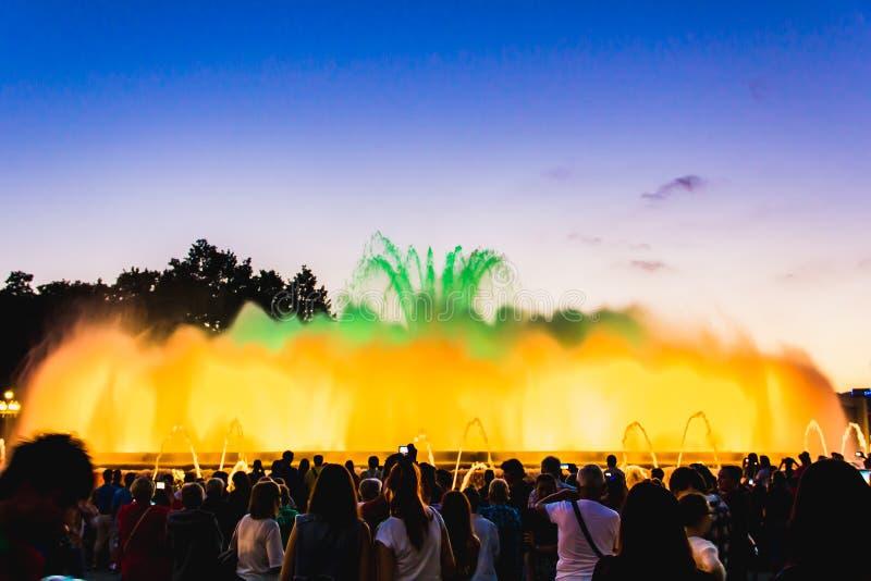 Sylwetka ludzie ogląda przy kolorowymi iluminować muzykalnymi fontannami w wieczór Lekki i wodny nocy przedstawienia występ obrazy stock