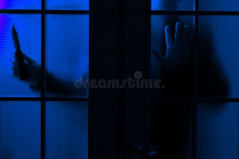 Sylwetka mężczyzna z nożem na tle szklany drzwi, selekcyjna ostrość zdjęcie royalty free