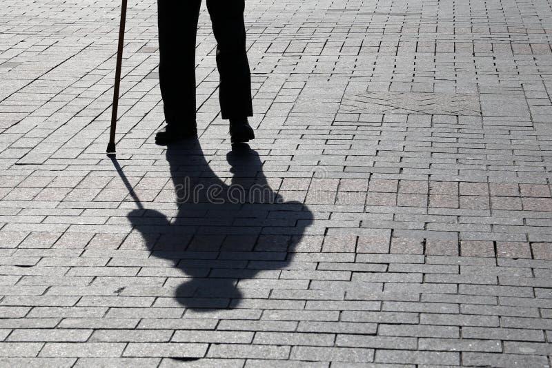 Sylwetka mężczyzny odprowadzenie z trzciną, tęsk cień na bruku obraz stock