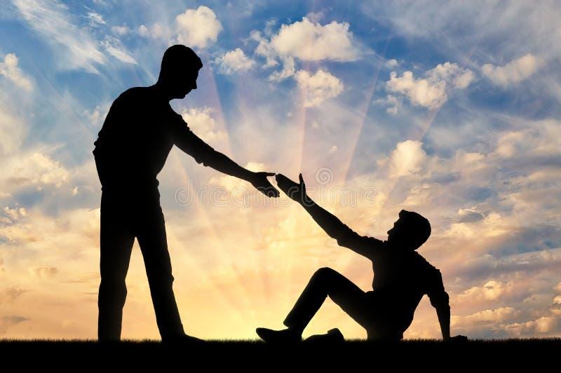 Sylwetka mężczyzna daje pomocnej dłoni inny mężczyzna który spadał ziemia fotografia royalty free