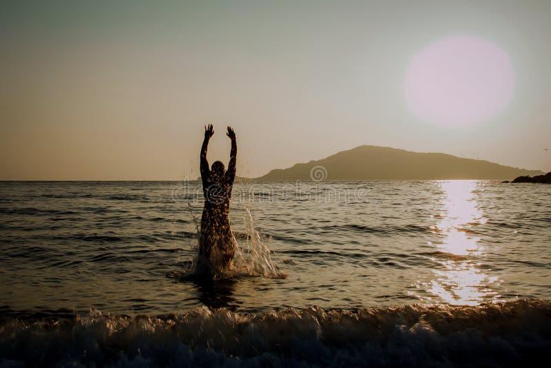 Sylwetka mężczyzna doskakiwanie z morza zdjęcie stock
