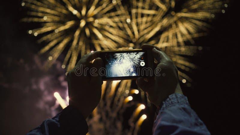 Sylwetka mężczyzna fotografuje fajerwerki przy nocnym niebem Piękny salut na cześć wakacje obraz royalty free