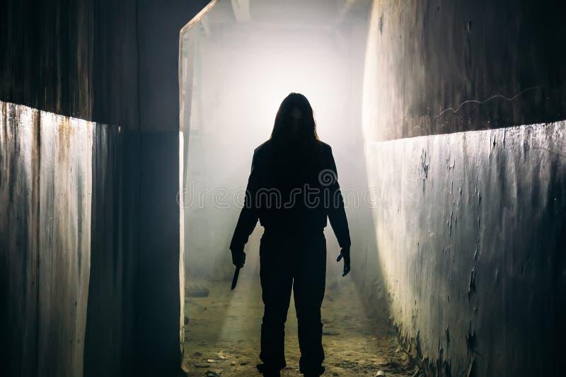 Sylwetka mężczyzna maniaczka, zabójca lub horroru morderca z nożem w ręce w ciemnym korytarzu przerażającym i strasznym zdjęcie royalty free