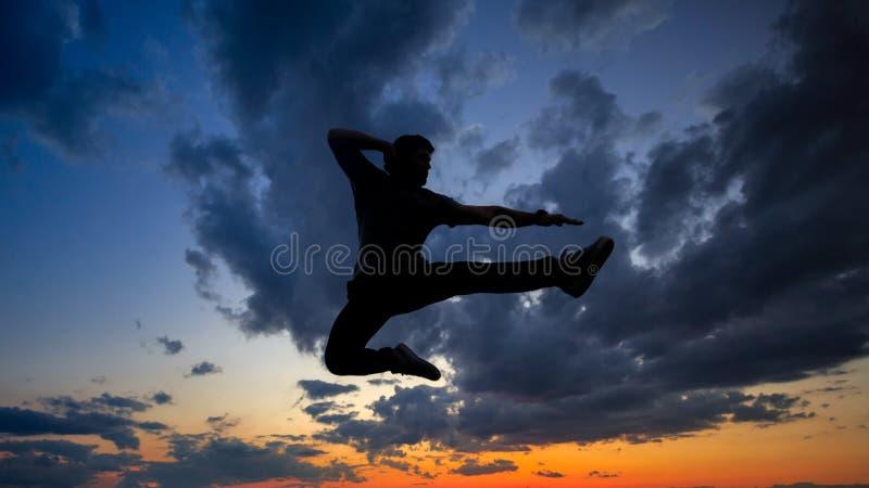 Sylwetka mężczyzna na dachu cloud słońca zdjęcie royalty free