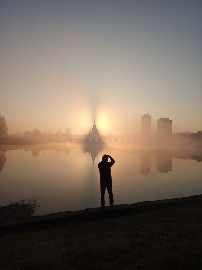 Sylwetka mężczyzna na tle wschód słońca i miasto widoku blisko jeziora i kościół zdjęcie stock