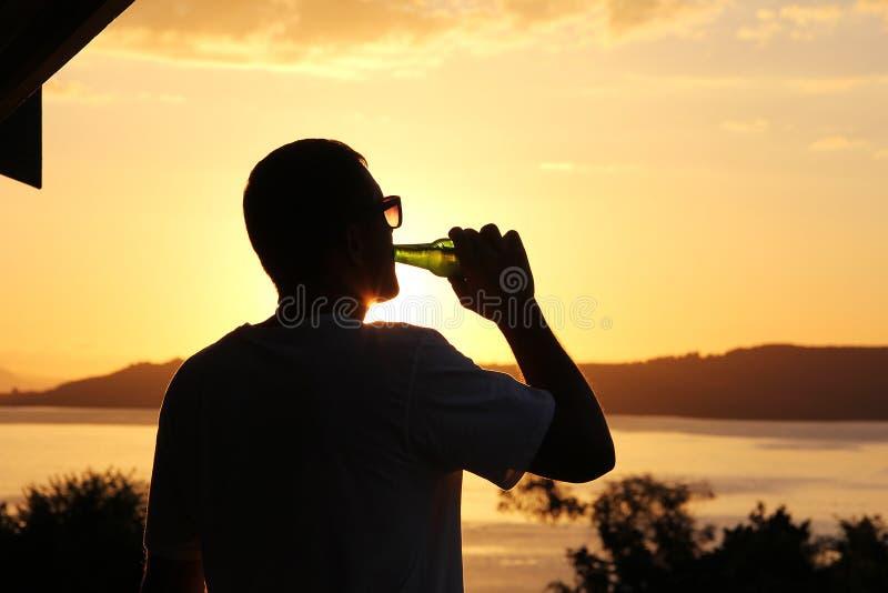 Sylwetka mężczyzna pije piwo przy zmierzchem obraz royalty free