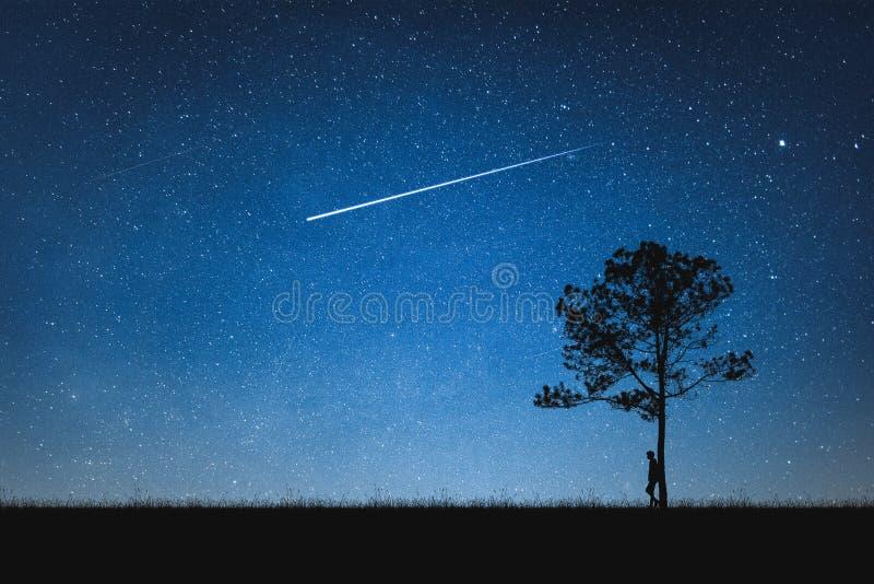 Sylwetka mężczyzna pozycja na górze i nocnym niebie z mknącą gwiazdą samotny pojęcie fotografia royalty free