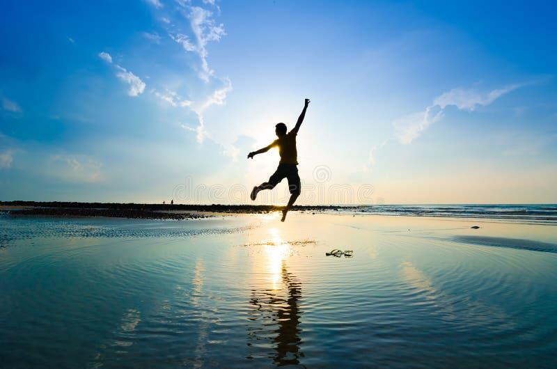 Sylwetka mężczyzna skacze nad słońcem zdjęcie royalty free