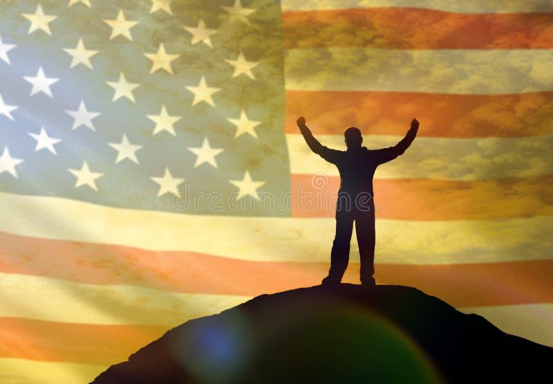 Sylwetka mężczyzna trzyma jego wręcza up na wierzchołku góra, przeciw tłu niebo flaga Ameryka, usa obrazy royalty free