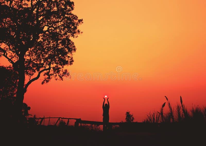 Sylwetka mężczyzna trzyma słońce obraz stock