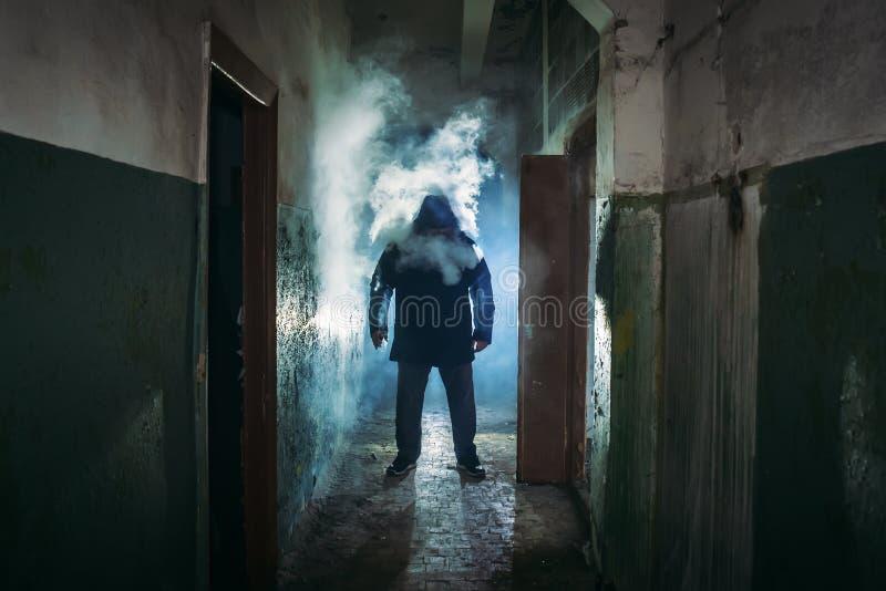 Sylwetka mężczyzna w chmura dymu pozycji w ciemnym strasznym korytarzu fotografia stock
