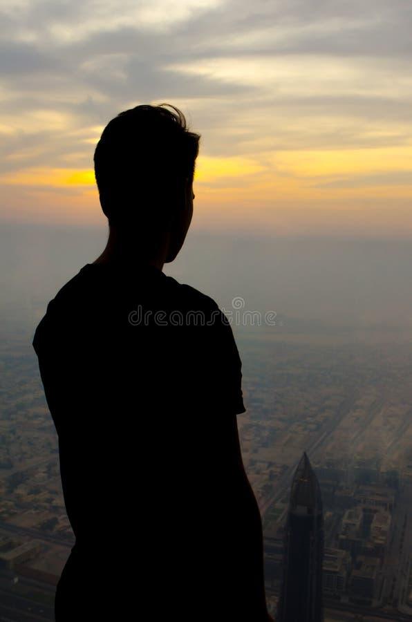 Sylwetka mężczyzna w cienia spojrzeniu od above nadmiernego miasta i zmierzchu zdjęcia royalty free