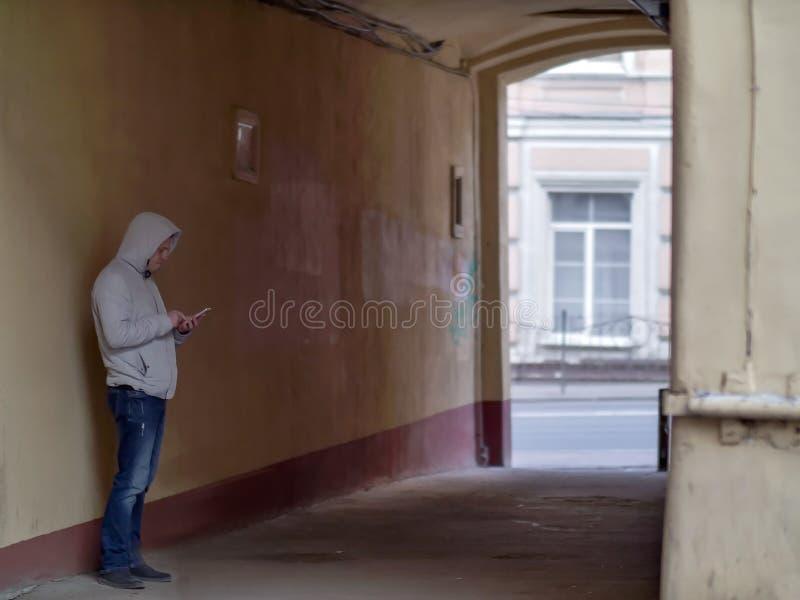 Sylwetka mężczyzna w kapiszonie w starym podwórze łuku obrazy royalty free