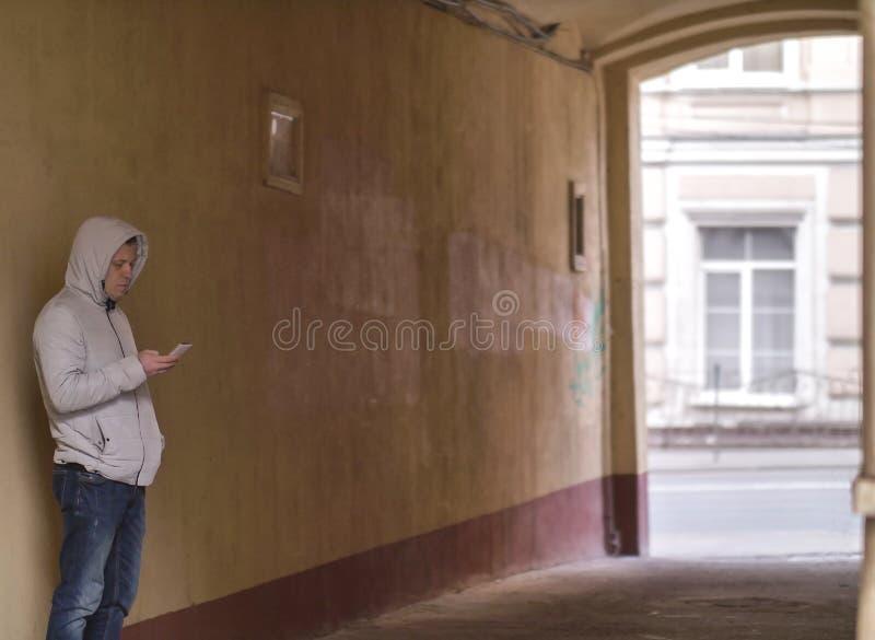 Sylwetka mężczyzna w kapiszonie z telefon pozycją w podwórzowym łuku fotografia stock
