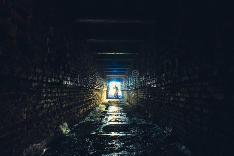 Sylwetka mężczyzna z latarką w zmroku brudnym ceglanym podziemnym tunelu lub kanalizacja korytarzu fotografia stock
