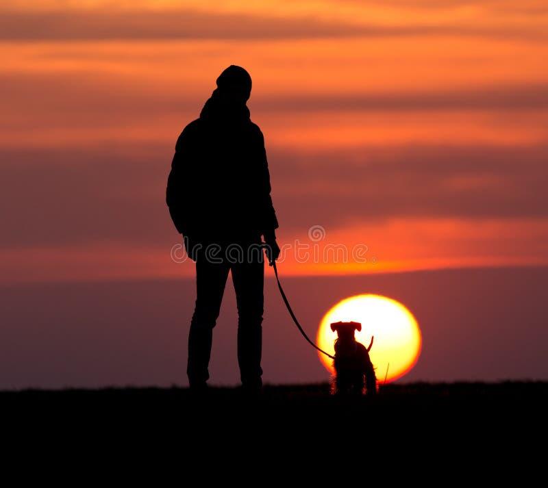 Sylwetka mężczyzna z psem przy zmierzchem zdjęcia royalty free