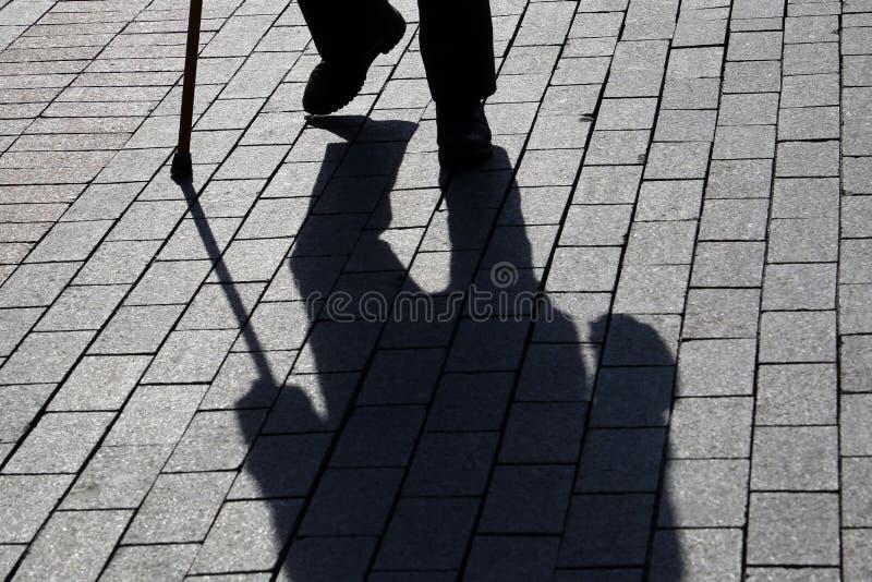Sylwetka mężczyzny odprowadzenie z trzciną, tęsk cień na bruku zdjęcia stock