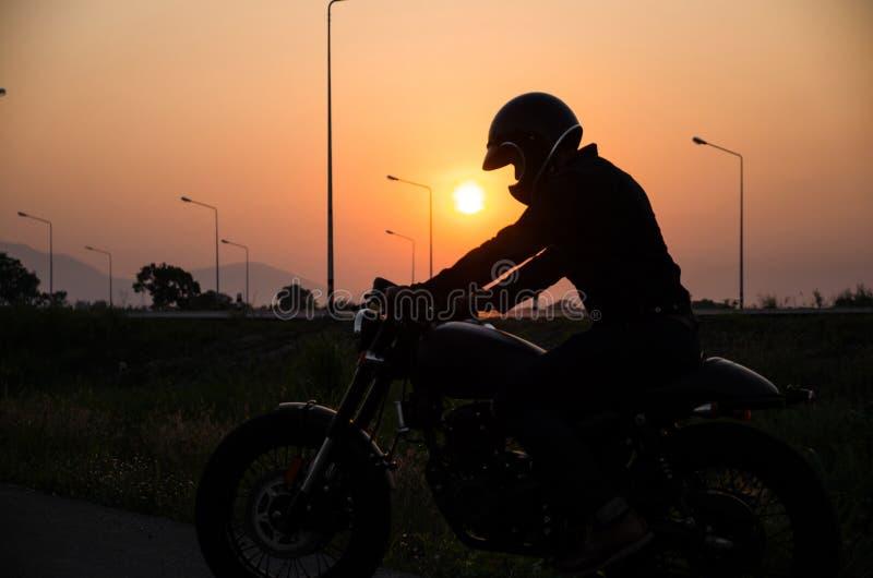Sylwetka mężczyzny rocznika jeździeckiego motocyklu setkarza cukierniany styl z hełmem fotografia stock