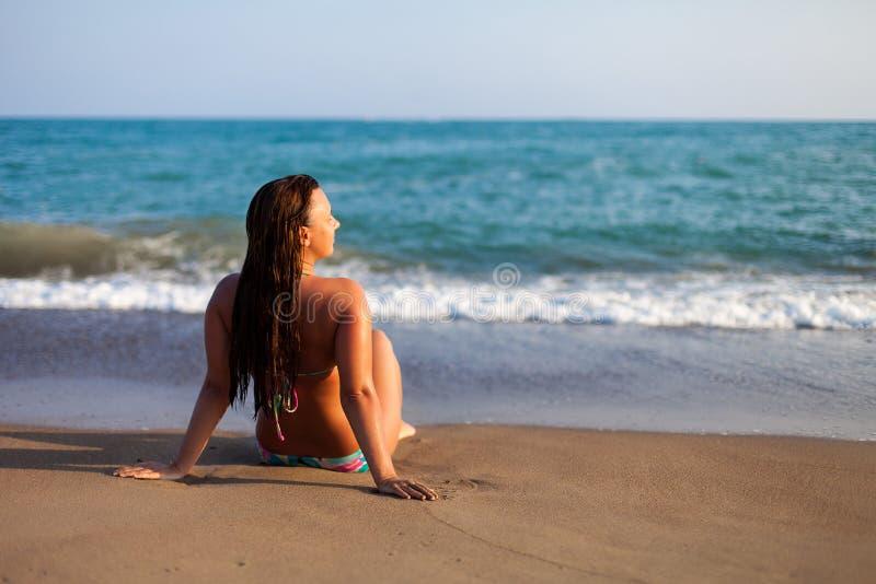 Sylwetka młoda kobieta na plaży Młodej kobiety obsiadanie przed nadmorski Dziewczyna relaksuje na plaży w bikini Kobieta zdjęcie stock