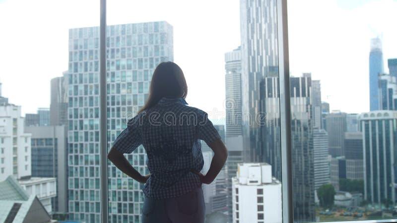 Sylwetka młoda kobieta podziwia miasto widok od okno w biurze zdjęcie royalty free