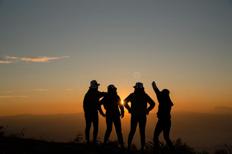 Sylwetka młoda kobieta stoi na wierzchołku góra która relaksuje słońcem przy wschód słońca od wschód słońca obrazy royalty free
