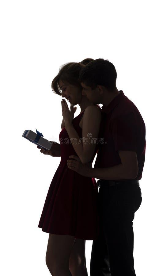 Sylwetka młoda para w miłości na białym odosobnionym tle, mężczyzna wchodzić na górę za kobietą robić niespodziance z pudełko ter obrazy royalty free