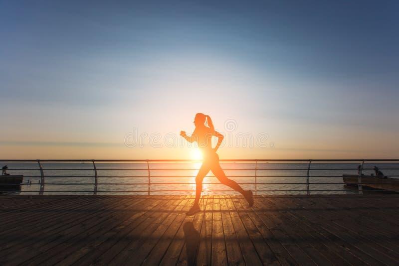 Sylwetka młoda piękna sportowa dziewczyna biega przy wschodem słońca nad morzem z długim blondynem w czerni ubraniach fotografia royalty free