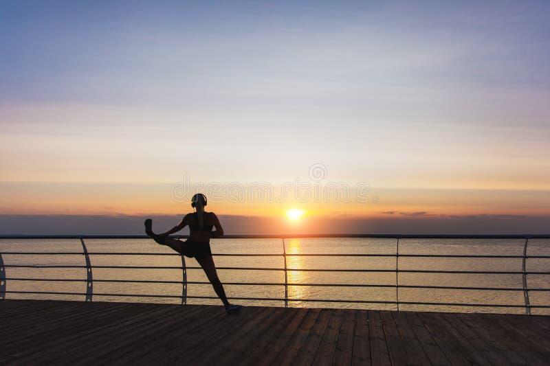 Sylwetka młoda piękna sportowa dziewczyna słucha muzyka i robi rozciąganiu przy wschodem słońca z długim blondynem w hełmofonach fotografia stock