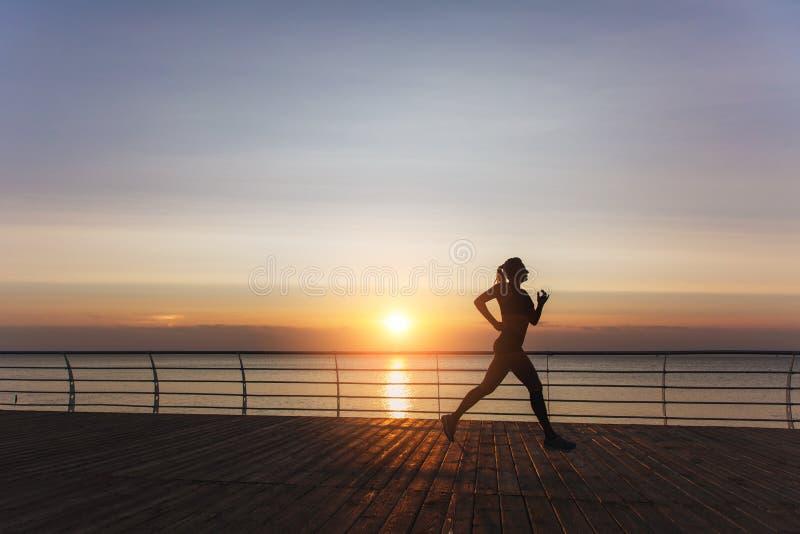 Sylwetka młoda piękna sportowa dziewczyna z długim blondynem który słucha muzyka i biega przy świtem nad s w hełmofonach, zdjęcia stock