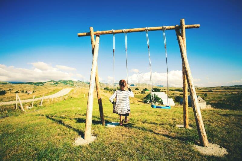 Sylwetka Młoda Szczęśliwa kobieta Na huśtawce, Huśta się Nad Andes górami, Drzewny dom, Montenegro, Durmitor park narodowy fotografia royalty free
