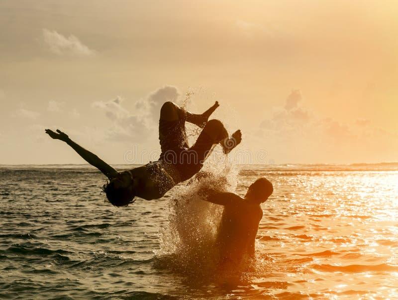 Sylwetka młodego człowieka doskakiwanie z oceanu obraz royalty free