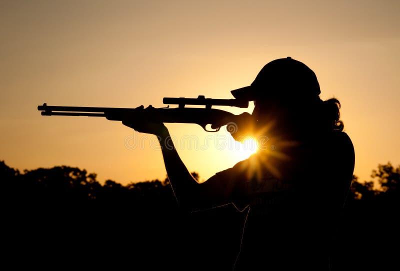 Sylwetka młodego człowieka strzelanina z karabinem obraz royalty free