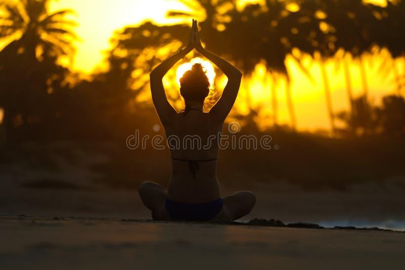 Sylwetka młodej kobiety ćwiczy joga na plaży przy zmierzchem fotografia royalty free