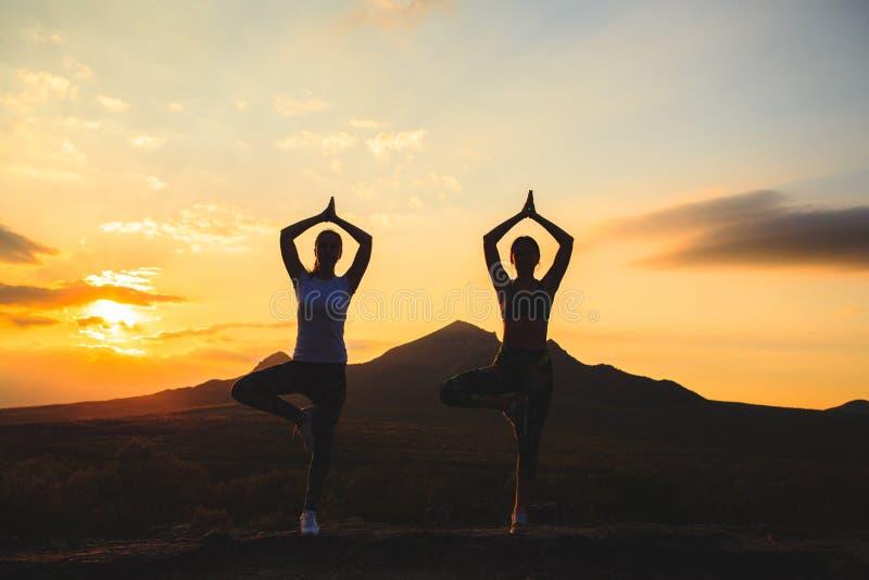 Sylwetka młodej kobiety ćwiczy joga pilates przy lub zmierzchem lub wschód słońca w pięknej halnej lokacji zdjęcie stock