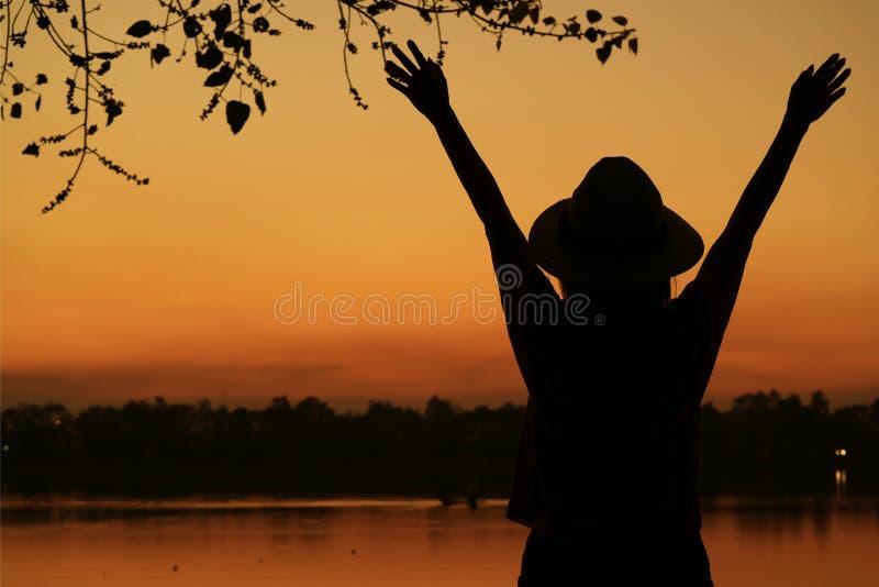 Sylwetka młodej kobiety dźwigania ręki przeciw pięknemu pomarańczowemu koloru zmierzchu niebu na jeziornym brzeg zdjęcia royalty free