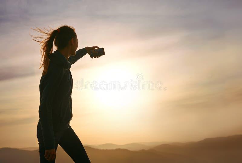 Sylwetka młodej kobiety pozycja na krawędzi góra i i brać fotografię na zmierzchu niebie i góry tle zdjęcie royalty free