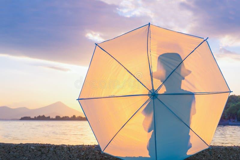 Sylwetka młody chłopiec modniś w kapeluszu z parasolem Dzieciak z parasolowym patrzeje seascape Podr??ny poj?cie Lato obraz stock