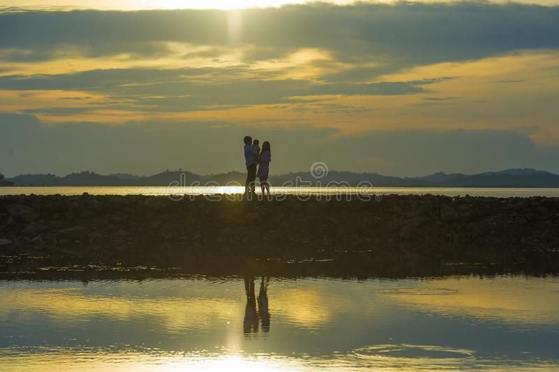 Sylwetka młody romantyczny pary mienie, bawić się z małym dzieckiem cieszy się zmierzch ma spacer przy plażą syna lub córki i obrazy stock
