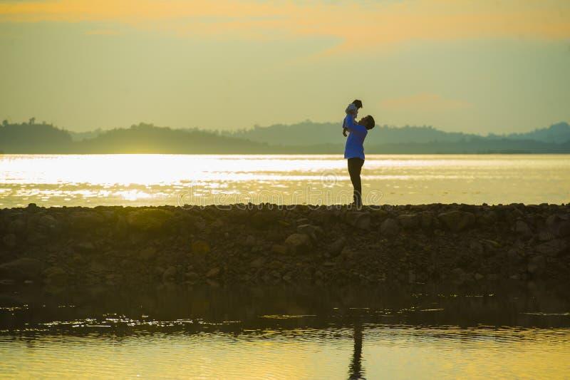 Sylwetka młody szczęśliwy mężczyzna z jego synem małą córką w jego rękach lub ojciec podnosi w górę dziecka przed morzem przy obraz stock