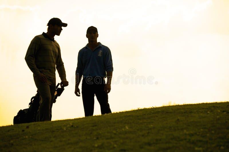 Sylwetka młodzi człowiecy stoi w polu golfowym z tramwajem zdjęcie stock