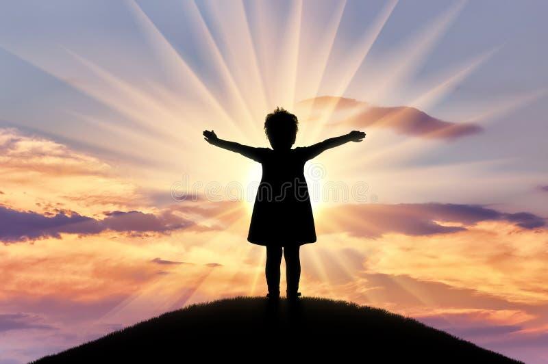 Sylwetka, mała szczęśliwa dziewczynki pozycja na wzgórzu na zmierzchu tle fotografia stock